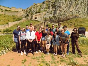 A group of students pose with Dr. Jeremy Hutton in front of the acropolis of Corinth on the UW Classics trip to Greece