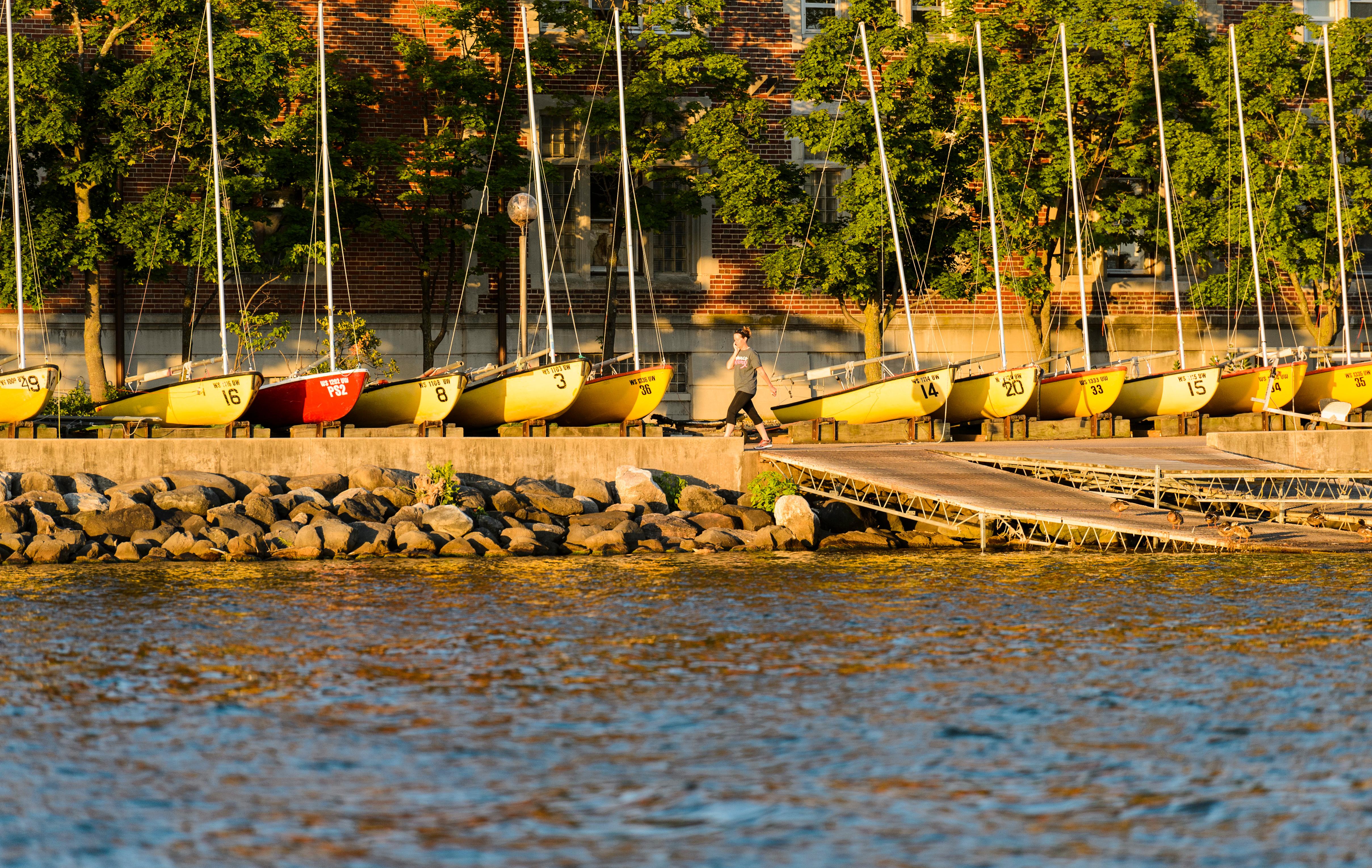 Runner jogs along Lake Mendota in front of Hoofer sailboats