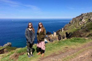 Lily Kobs and another young woman standing on a hill overlooking the sea at Botallack Mine in Cornwall