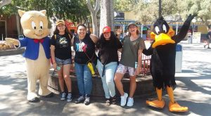 A group of young women posing with Daffy Duck and Elmer Fudd at Six Flags