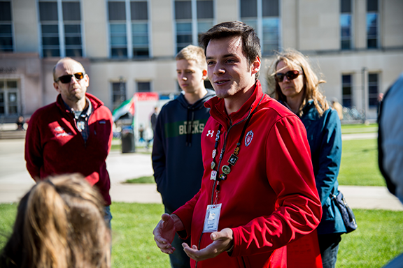 A student tour guide talks to a group on Library Mall